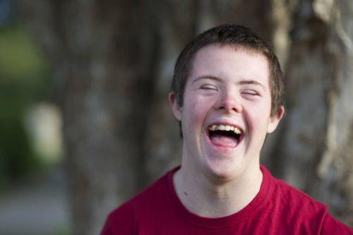ein fröhlicher Junge mit Downsyndrom